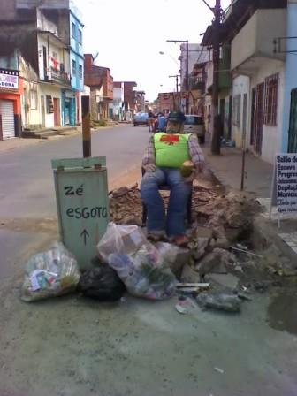 Zé Esgoto descansa sobre o monte de entulho deixado pela Emasa. O buraco também ainda está lá