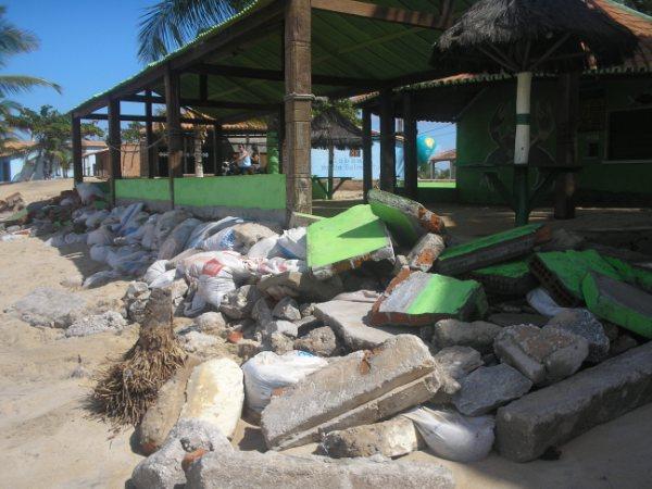 Barracas são destruídas pelo mar.